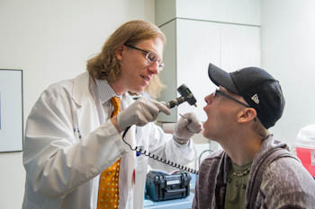 Nathaniel Treister, DMD, an oral expert with Dana-Farber/Brigham and Women's Cancer Center, checks a patient during an oral exam.