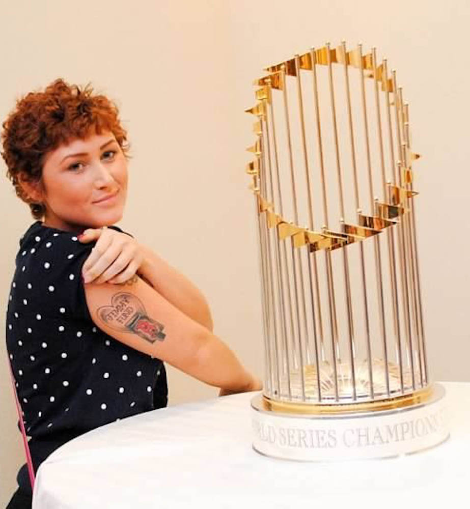 Fox with her Jimmy Fund/Red Sox tattoo, next to the 2013 World Series trophy