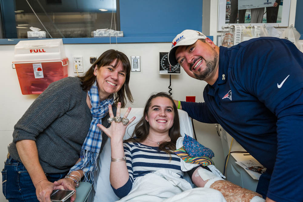 Former New England Patriots player Joe Andruzzi visits with Kelly Fabrizio (center) and her mom while Kelly donates at the Kraft Family Blood Donor Center.