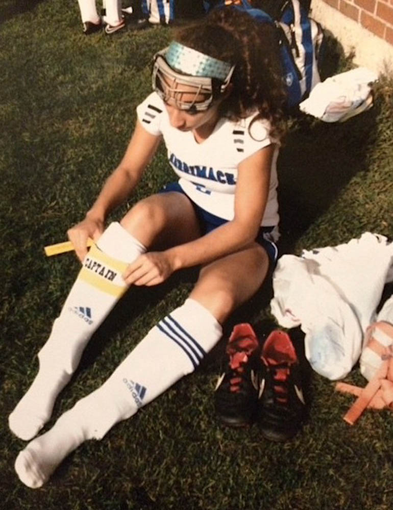 "Dana slides on her ""captain"" band during a high school field hockey game in Merrimack, N.H."