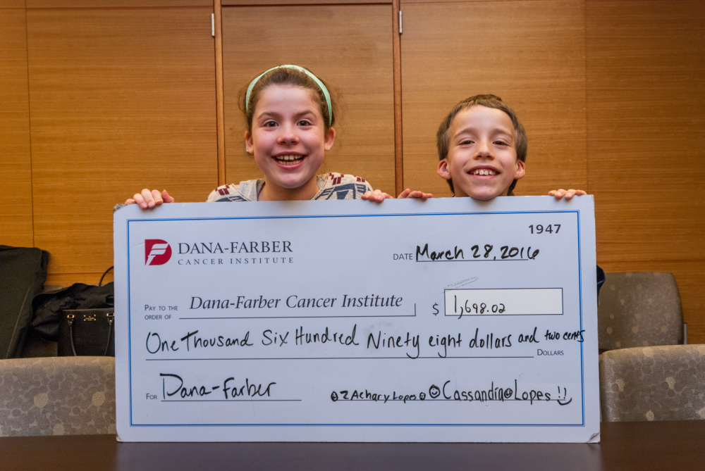 Zach and Cassie Lopes with check