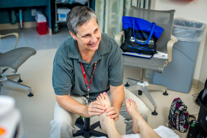 Theresa Ochenkoski, LMT, offers foot reflexology to a patient.