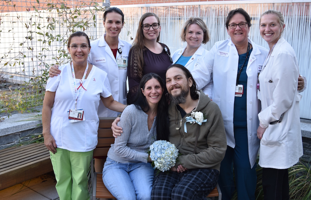 When it was clear that his disease was terminal, in Fall 2017, social workers Mellissa Rearick, MSW, LICSW, of Dana-Farber Milford and Cheryl Mitchell, MSW, LCSW, of Milford Regional Medical Center (where Anthony often stayed as an inpatient) headed up arrangements for the couple's wedding on Oct. 18 – one day after Anthony proposed. The rings and gluten-free cake were donated and the Milford Regional chaplain performed the ceremony. Anthony's oncologist, Natalie Sinclair, MD, and other caregivers were also in attendance. Photo by Jennifer Shepherd