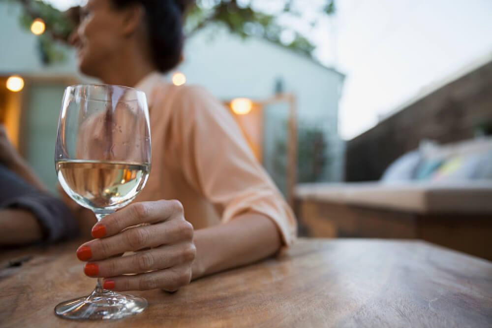 Woman drinking wine on a patio.