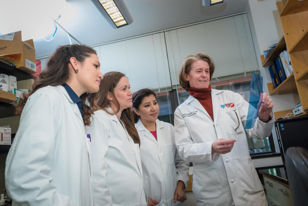 Dana-Farber's Elizabeth A. Mittendorf, MD, PhD, looks at a scan with others in the Breast Immunology Laboratory.