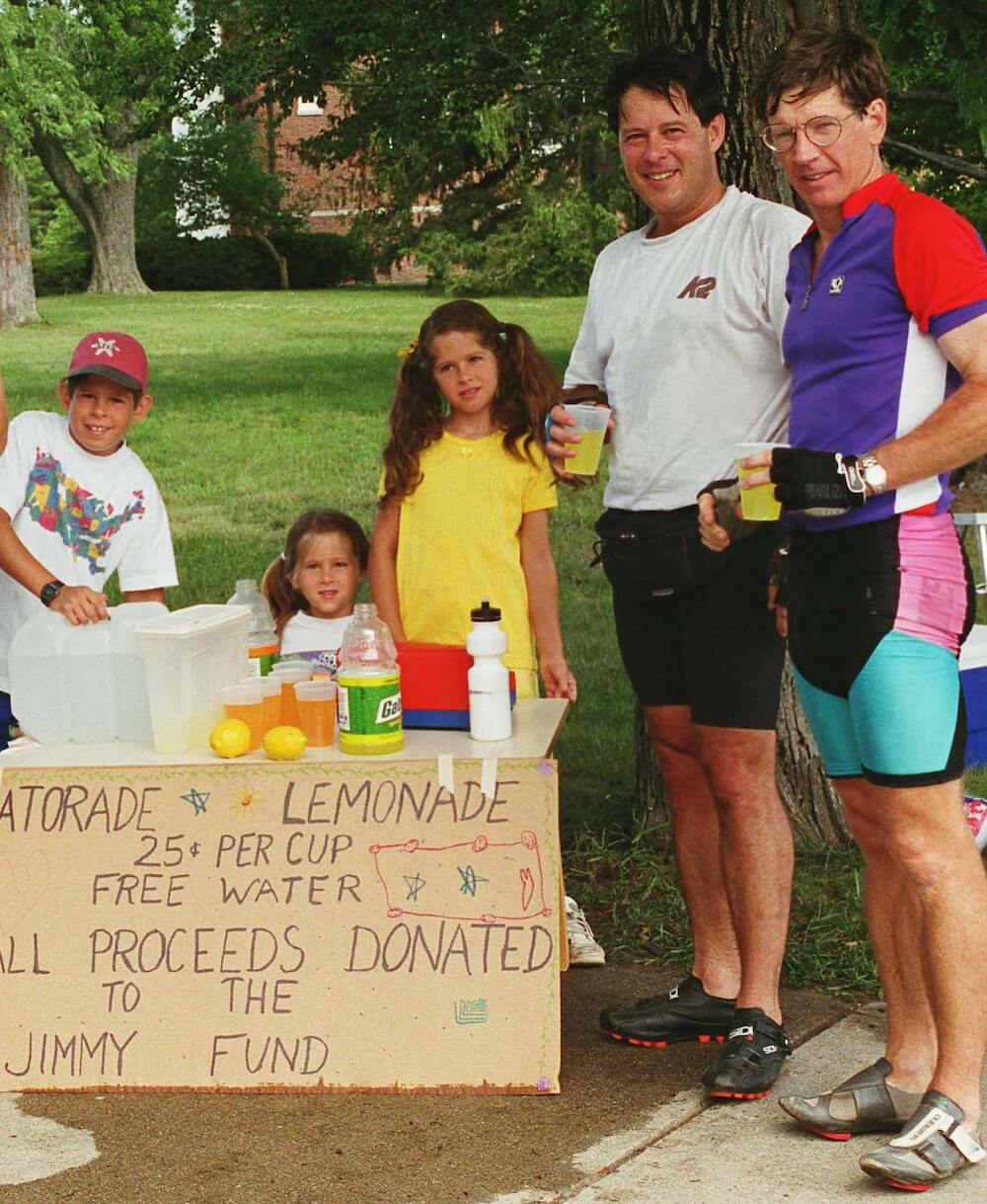 Team co-founders Dave Mittelman (second from right) and Greg Shoukimas (far right) enjoy some refreshment in 1995 at a lemonade stand set up to fundraise for the PMC  by Mittelman's children (from left) Andy, Melissa, and Jamie. The children would later became PMC riders themselves.