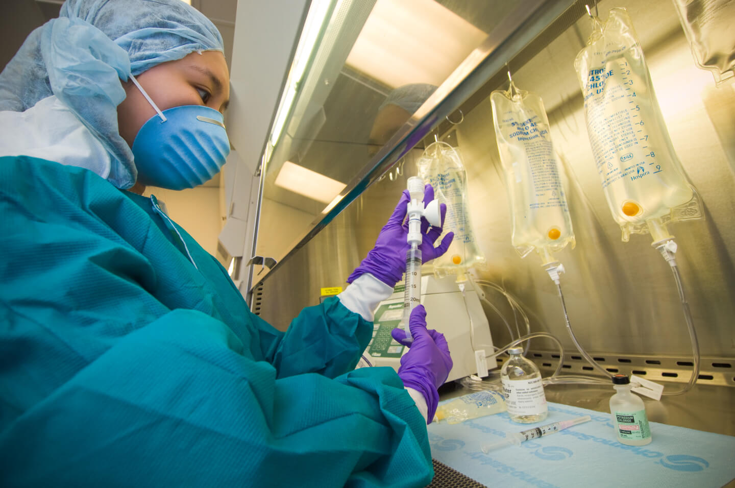 A pharmacy technician prepares infusion medication in a biological safety cabinet.